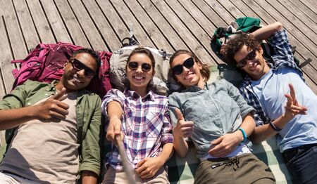 A group of friends or tourists with backpacks lying on wooden terrace and taking picture by selfie stick