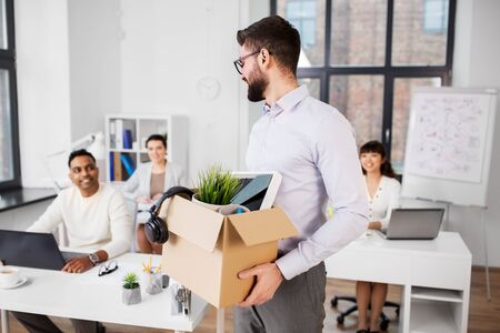 Happy smiling male office worker with personal stuff