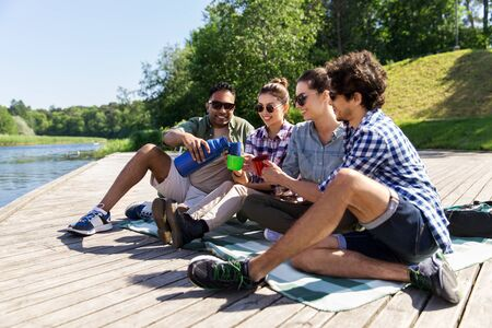 Happy friends drinking tea  outdoors in summer park Imagens