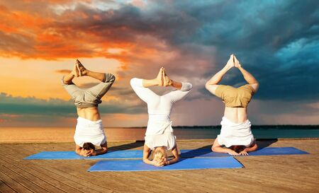 People making headstand pose on mat on river on sea pier over sunset 写真素材
