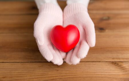 Hands in pale pink  gloves holding red heart over wooden boards Фото со стока