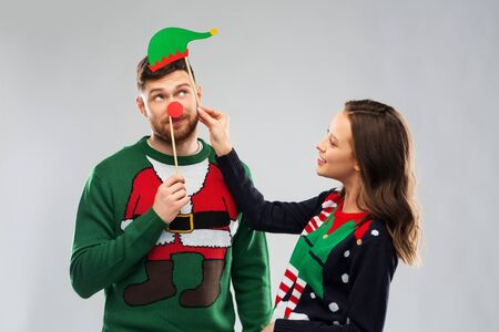Happy couple in ugly sweaters posing with party props