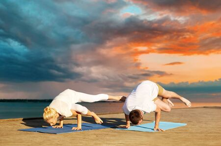 A couple making side crane pose on mat on sea pier over sunset