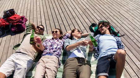 Friends drinking beer and cider on wooden terrace in summer Stock Photo