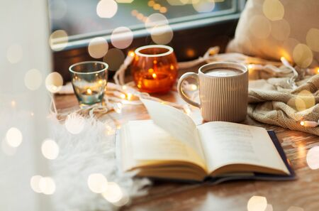 Book, cup of coffee or hot chocolate and candles with garland on window sill