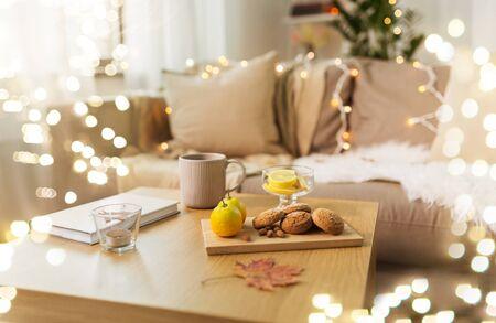oat cookies, book, tea and lemon on table at home Standard-Bild