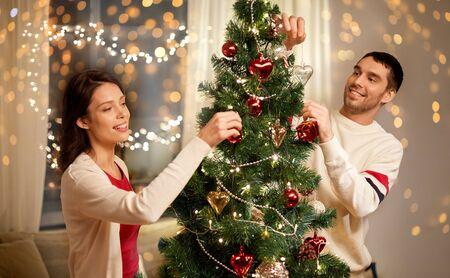 Pareja feliz decorando el árbol de navidad en casa