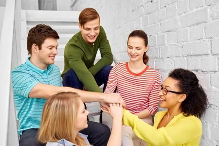 Smiling teenage friends or students stacking hands hanging out on stairs Stock Photo