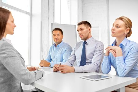International team of recruiters having interview with female employee at office Stock Photo