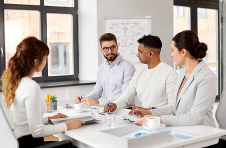 International team of recruiters having interview with asian female employee at office