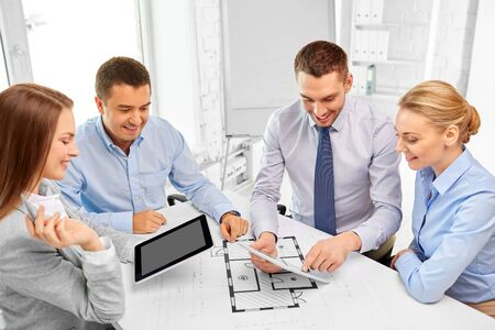 Happy team of architects discussing blueprint at office Reklamní fotografie