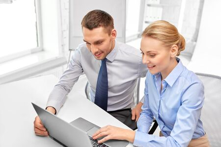 Happy businessman and businesswoman with laptop computer at office