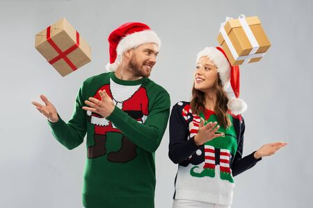 Happy couple in santa hats with christmas gifts at ugly sweater party Stock Photo