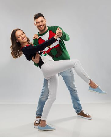 couple dancing at christmas ugly sweater party Stockfoto - 130054616