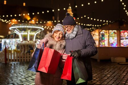 Happy senior couple with shopping bags at christmas market souvenir shop on town hall square