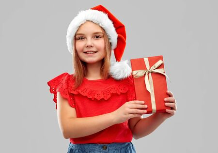 Smiling girl posing in santa helper hat with gift box over grey Stock Photo
