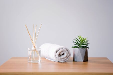 Aroma reed diffuse, bath towel and succulent on wooden table Stock Photo