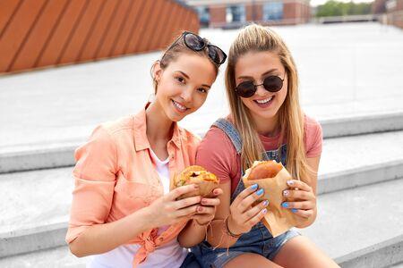 Happy  smiling teenage girls or best friends in sunglasses eating burgers on city street in summer