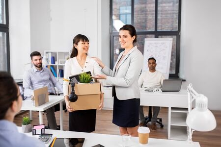 Female employee with personal stuff meeting colleagues at office