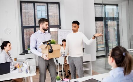 Executive seeing off sad fired male office worker holding box of his personal stuff