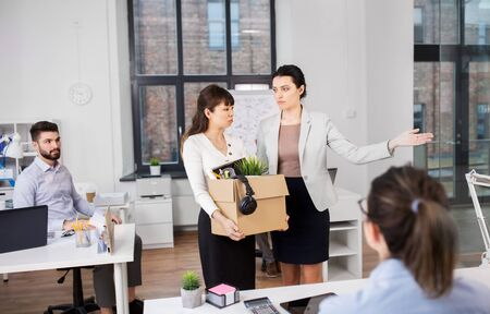 Executive and sad fired asian female office worker holding box of his personal stuff