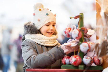 Happy little girl choosing christmas balls at market in winter Stock fotó