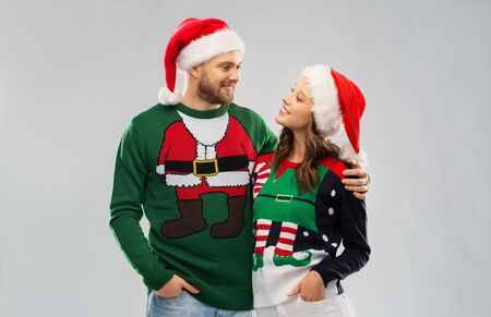 Portrait of happy couple in santa hats at ugly sweater party Stockfoto