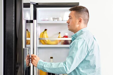 Middle-aged man looking for food in fridge at kitchen 版權商用圖片