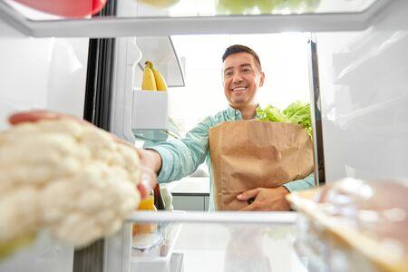 Hombre de mediana edad sonriente con nuevos alimentos comprados en una bolsa de papel poniendo coliflor a la nevera en casa