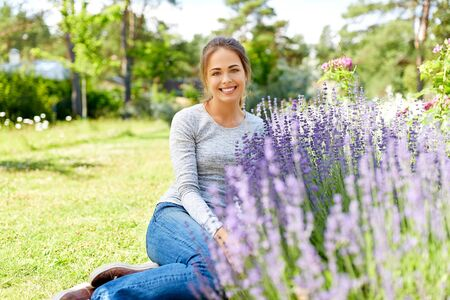 Happy young woman sitting on grass near lavender flowers on summer garden bed 版權商用圖片