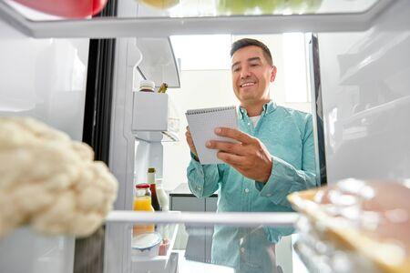 man making list of necessary food at home fridge