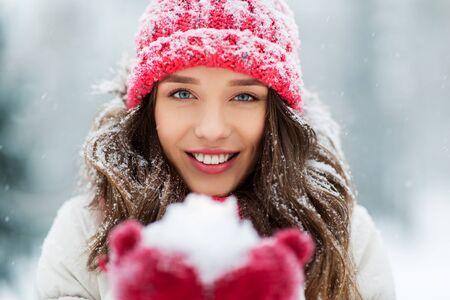 Portrait de jeune femme avec de la neige dans le parc d'hiver