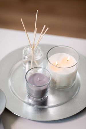aroma reed diffuser an candles burning on tray