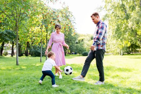 happy family playing soccer at summer park Stockfoto