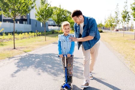 happy father and little son riding scooter in city 免版税图像