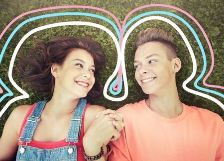 happy teenage couple lying on grass at summer Reklamní fotografie