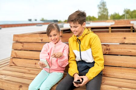 children with smartphones sitting on street bench
