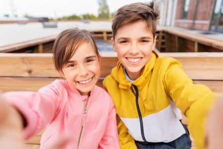 children sitting on street bench and taking selfie