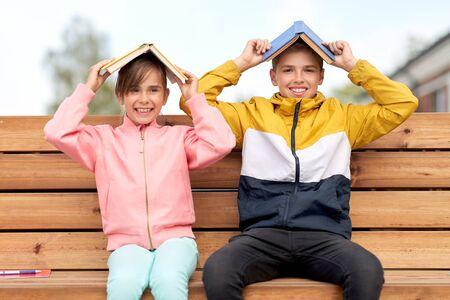 Schulkinder mit Büchern, die sich im Freien amüsieren