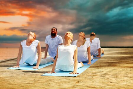 group of people making yoga exercises outdoors 写真素材