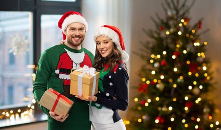 winter holidays, celebration and people concept - happy couple in santa hats and ugly sweaters with gifts at home over christmas tree lights background