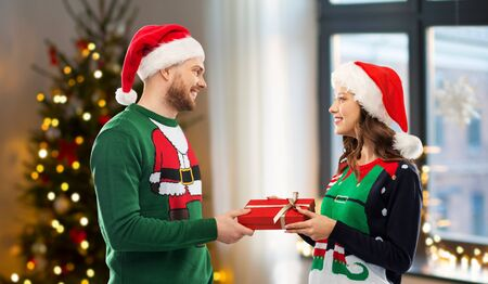 winter holidays, celebration and people concept - happy couple in santa hats and ugly sweaters with gift box at home over christmas tree lights background Stockfoto