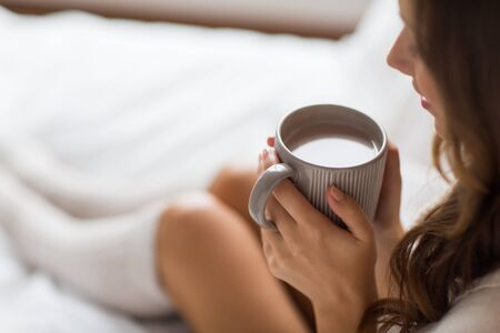 close up of happy woman with cup of coffee at home
