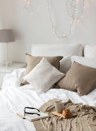 concept de confort, hygge et intérieur - café, croissant, couverture et livre sur le lit dans une maison confortable