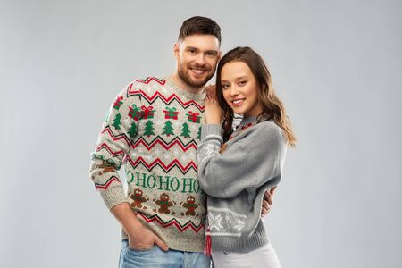 christmas, people and holidays concept - portrait of happy couple at ugly sweater party