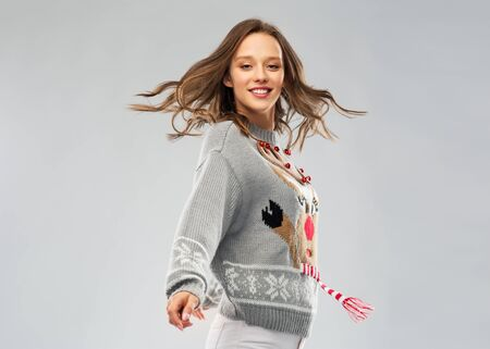 christmas, people and holidays concept - happy young woman in jumper with reindeer pattern dancing at ugly sweater party Stockfoto