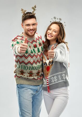 christmas, people and holidays concept - happy couple hugging at ugly sweater party Stockfoto