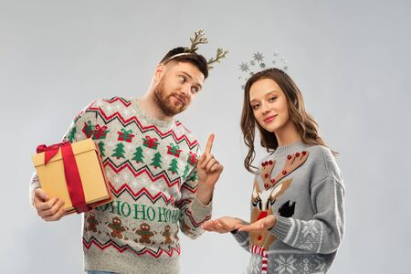 people and holidays concept - portrait of happy couple with christmas gift at ugly sweater party Stockfoto