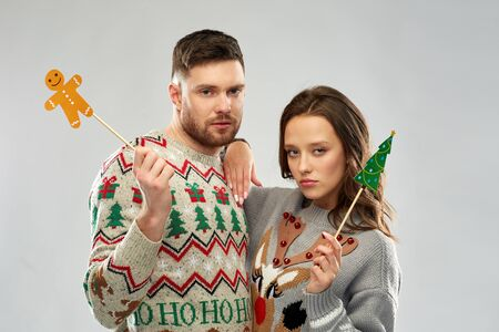 christmas, photo booth and holidays concept - sad couple in ugly sweaters posing with party props