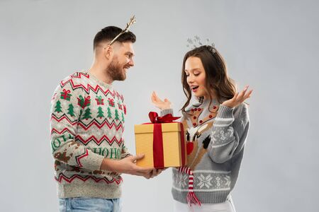 people and holidays concept - portrait of happy couple with christmas gift at ugly sweater party Stockfoto - 129889215
